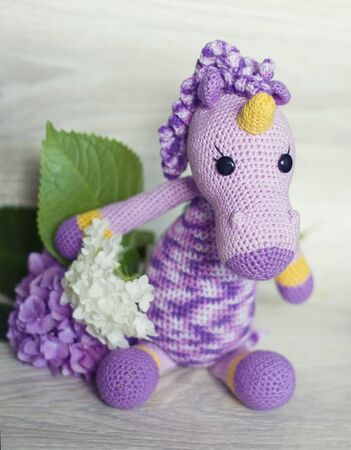 Hooked unicorn lilac of melange threads are yellow elements. A nice toy handmade. Photo of hydrangea. 版權商用圖片