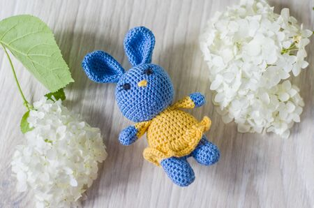 Crocheted hare of blue in yellow dress. A nice handmade toy. Photo of hydrangea. 版權商用圖片
