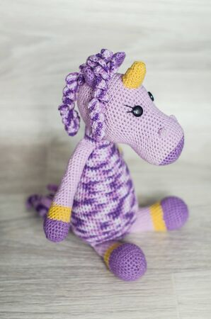 Crocheted unicorn lilac of melange threads are yellow elements. A nice toy handmade. 版權商用圖片