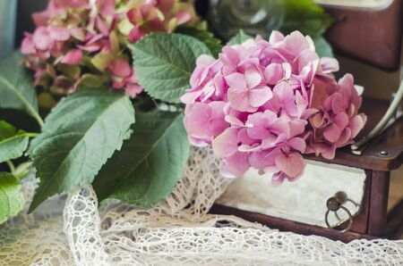 Still life of hydrangea, ancient mirror on knitted crocheted napkin. Vintage composition in the style of chebbishik.