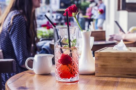 Photo mojito from strawberries. Red rose in a white vase in the background. Silhouetted by a girl.