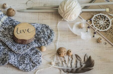 Composition with the inscription Love, wooden and knitted elements. Cozy photo in the style of a hugge.
