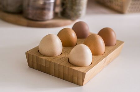 Wooden holder with chicken eggs on table. Six brown eggs.