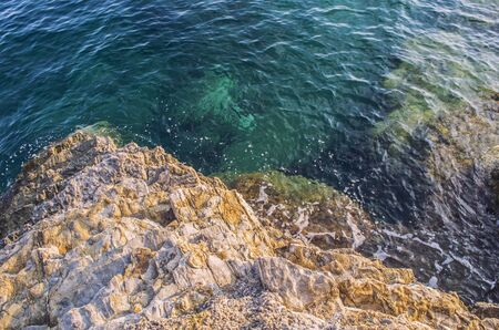 Turquoise shallow water surface and rocks stones on sea floor. Shallow transparent green sea water rocks at the bottom