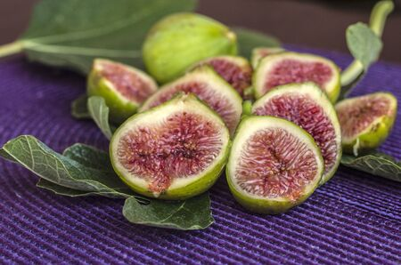 Fresh sliced figs on a green leaves. Tropical fruit. Top viev.