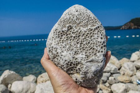 Natural pumice stone in hand on sea background. Natural resources for beauty. Stok Fotoğraf