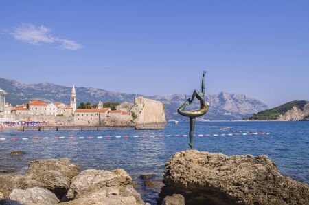 Statue of a ballerina Dancer of Budva against the Old Town of Budva. Panoramic view. Medieval cities in the Mediterranean. Resort of Adriatic Riviera.