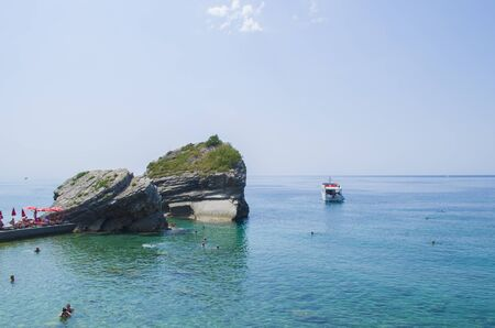 Rocky shore in the middle of the sea with swimming people Stok Fotoğraf