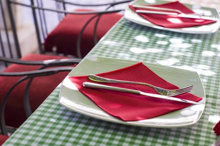 Table setting with plates and cutlery, close up. Plate and fork with knife with napkin.