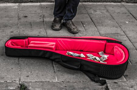 Cello case with red velvet with money. Photo - street musician. Black and white photo.