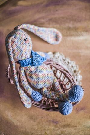 A knitted rabbit in pastel colors sits in a basket with vines. Vintage photo of handmade toys.