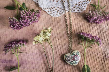 Sedum Spectabile and vintage brass pendant made of enamel hearts.Crocheted napkin on a pink background. Reklamní fotografie
