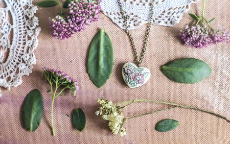 Sedum Spectabile and vintage brass pendant made of enamel hearts.Crocheted napkin on a pink background. Stok Fotoğraf