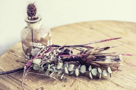 Glass vintage bottle with thistle and dried flowers.Hugge interior decoration.Vintage photo.