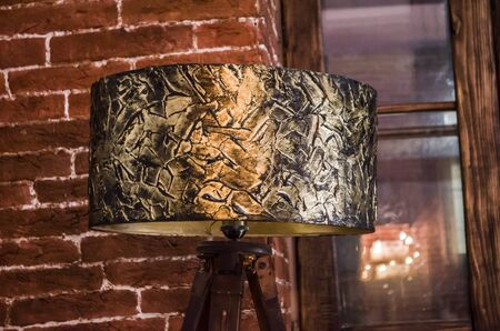 Handmade table lamp with bronze floor lamp. Lighting in a cozy interior. Texture paste and bronze paint for decoration. Standard-Bild