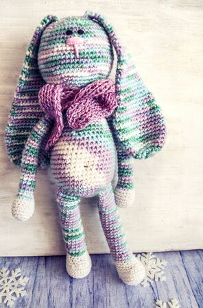 A knitted rabbit in pastel colors. Vintage photo of handmade toys.