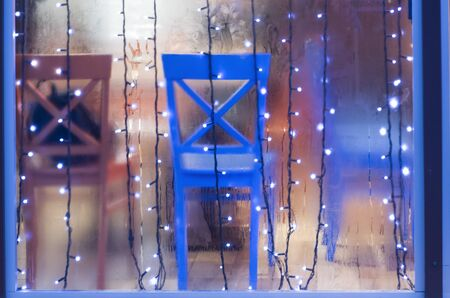 Colored chairs in the showcase of rain. Photo festive lights over glass.