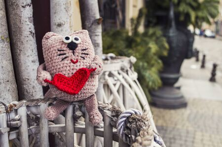 Adorable crocheted cat with red heart on old city background. Valentine day concept.