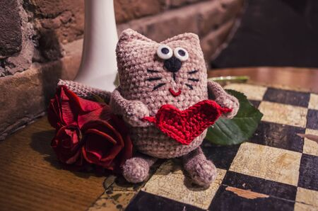 Adorable crocheted cat with red heart with red rose on chess vintage background. .Valentine day concept.