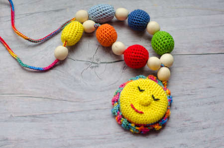 Necklace made from knitted beads and toys for the baby sitting in a sling. Knitted beads. Sling necklace. Imagens