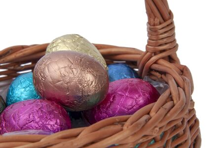 chocolate easter eggs in wooden basket isolated on the white Foto de archivo