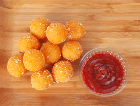 Cheese balls snacks deep fried on the wooden background with sauce