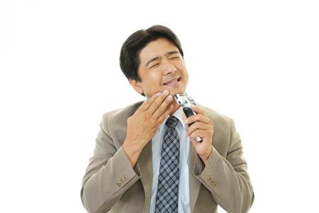 man shaving with electric razor photo