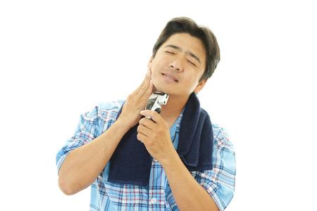 electric razor:  man shaving with electric razor