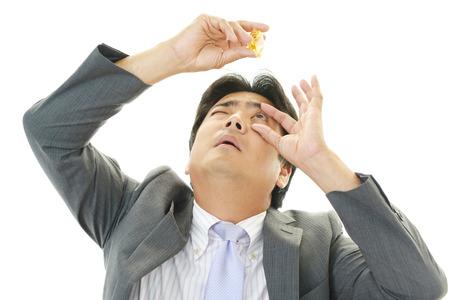 目薬を入れる男 写真素材