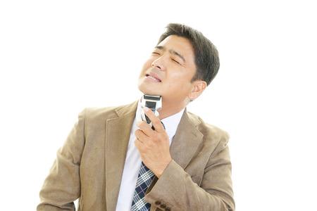 electric razor: man shaving with electric razor Stock Photo