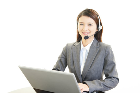 Young attractive customer services operator talking on headphones, using laptop.