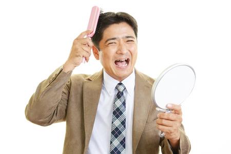 Asian man looking at his hair in mirror photo