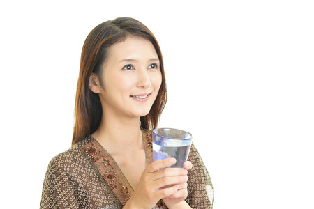 young woman drinking a glass of water photo