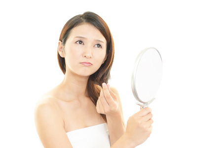 Woman looking at herself in a hand mirror photo