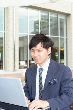 liveliness: Smiling businessman using laptop