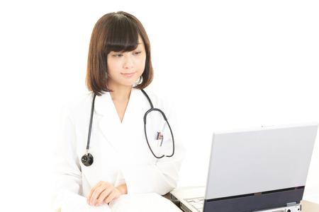 Asian female doctor using laptop photo