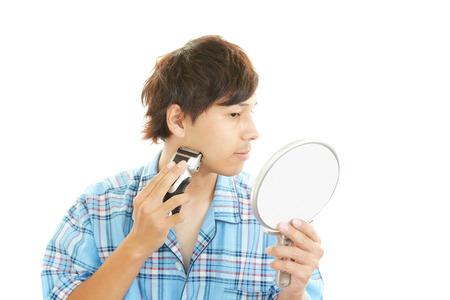 poise: man shaving with electric razor Stock Photo