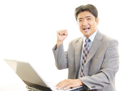ラップトップを使用して笑顔の実業家