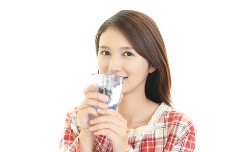 water resources: young woman drinking a glass of water
