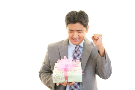 Joyful man holding presents in hands photo