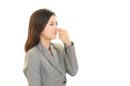 unpleasant: Portrait of pretty young woman closing covering nose