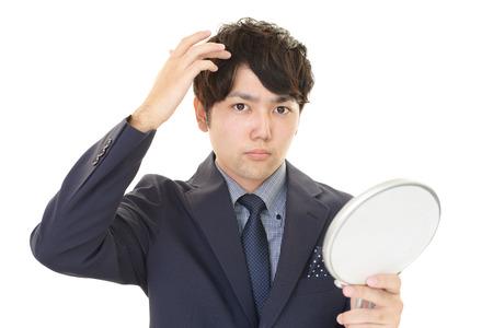 salaried: Asian man looking at his hair in mirror Stock Photo