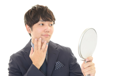 Asian man looking at his hair in mirror Stock Photo