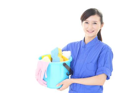 mujer limpiando: Una mujer sonriente con un cubo