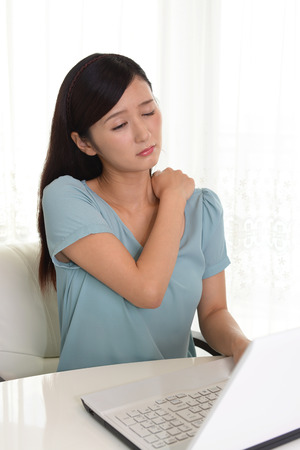 dolor hombro: Mujer que tiene un dolor en el hombro
