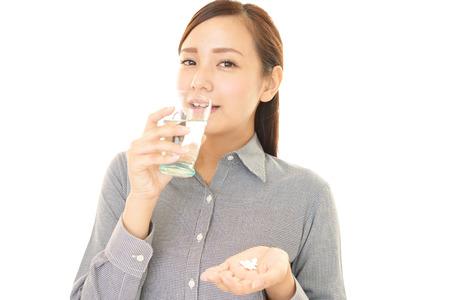 Frau, die Ergänzungen trinken