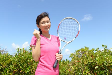 salud y deporte: Mujer sonriente con una raqueta de tenis Foto de archivo