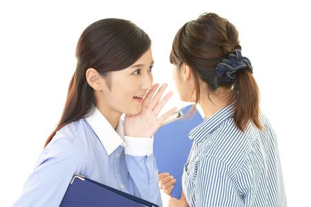 telling: Woman telling secret to her friend