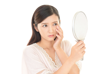 woman mirror: Woman with an uneasy look. Stock Photo