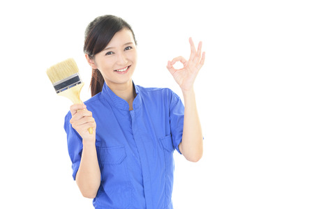 liveliness: Smiling female worker with a paint brush